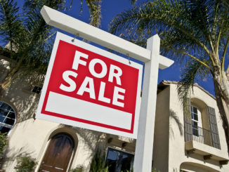 "A """"For Sale"" sign sits in front of a two-story home with palm trees."