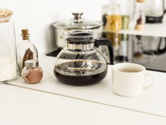 On the counter in a kitchen, a close up view of coffee maker, a cup and glass jars near a stove.