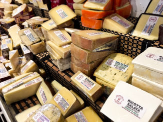 A variety of cheeses are on display.