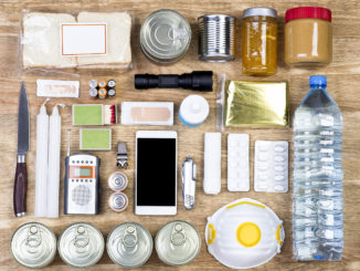 Overhead view of a wooden table with items useful for an emergency including a water bottle, candles, batteries and canned food.