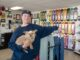 Lucas Underwood holding the small dog, Ozzi, next to skateboard parts.